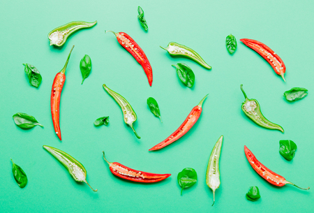 Above view at cutted Chili pepper and basil on green background