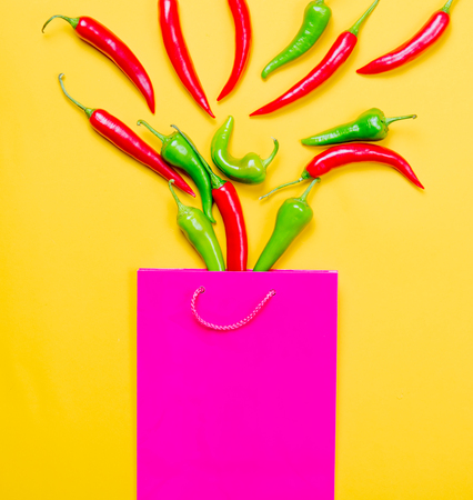 capsaicin: Above view at Chili pepper and shopping bag on yellow background Stock Photo