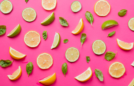 cutted: Above view at cutted lemons and limes on pink background Stock Photo