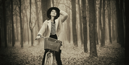 portrait of a young woman with a bicycle standing in the middle of the forest