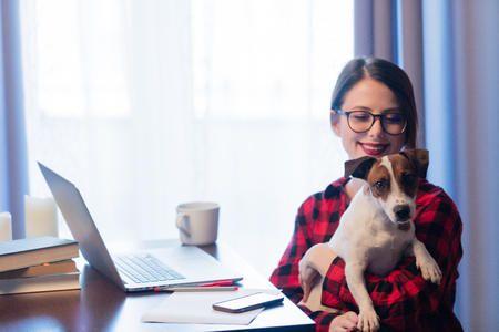 Young businesswoman at home interior with dog