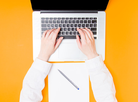 Businesswoman making notes with laptop and paper on yellow background