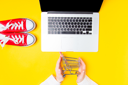 Female hands with shopping cart near laptop and gumshoes on yellow background