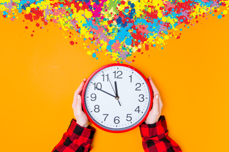 big shirt: Female hands holding huge clock with color inpiraton on yellow background Stock Photo