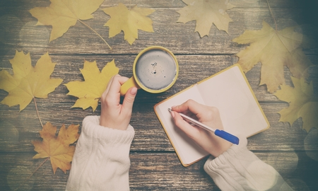 Female hand writing something in notebook near cup of coffee and autumn maple leaves Stock Photo