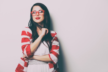 portrait of the beautiful young woman with eyeglasses on the white background