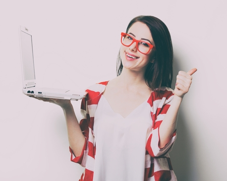 portrait of the beautiful young woman with laptop on the white background