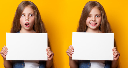Beautiful young girl with white board on yellow background. photo