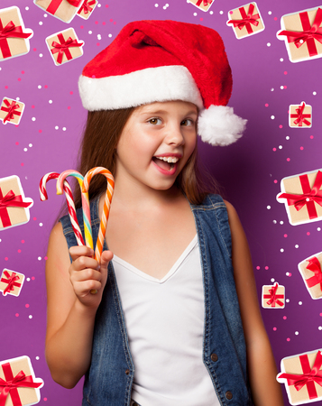 Beautiful young girl in red Santas hat with candy on violet background. photo
