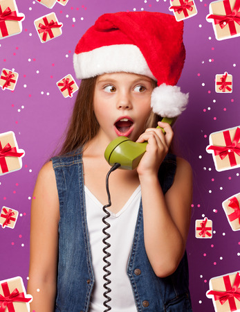 Beautiful young girl in red Santas hat with green handset on violet background. photo