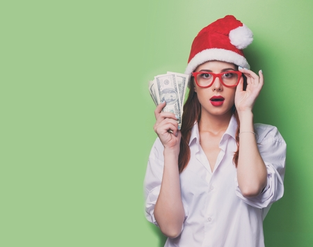 Portrait of a women in christmas hat with money on green background. Stock Photo