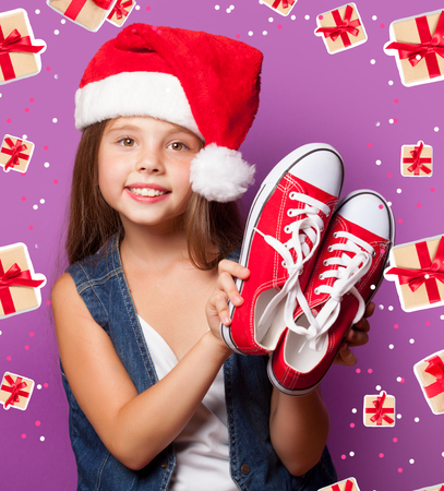 Beautiful young girl in red Santas hat with gumshoes on violet background. photo