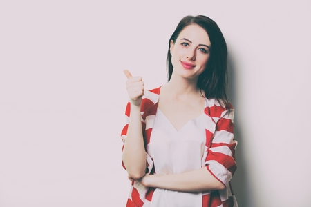 portrait of the beautiful young woman in striped clothes on the white background