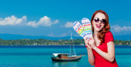 Happy redhesad girl in sunglasses with flip flops and red dress on blue background