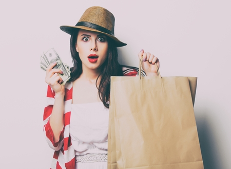 papel filtro: portrait of the beautiful young woman with shopping bags and money on the white background Foto de archivo