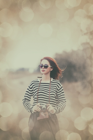 photgraphy: Portrait of a young redhead girl in sunglasses and camera at outdoor in autumn time Stock Photo