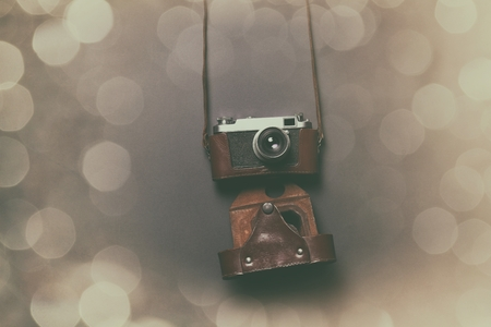 Retro camera in leather case lying down on grey background