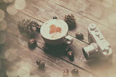cinnamon swirl: Cup of coffee with heart shape and pine cone with acorn and camera on wooden background Stock Photo