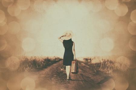 brunette fille avec une valise à la route de campagne