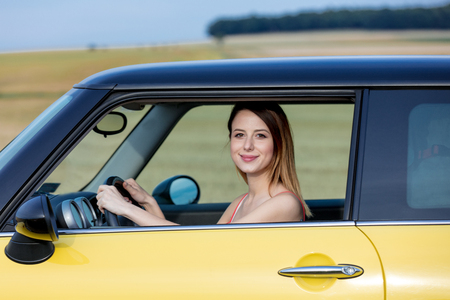 Young adult girl sitting in a new yellow just bought car