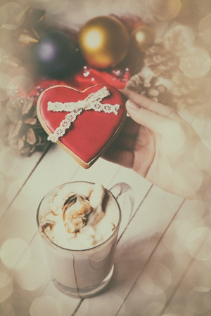 photo of the female hand holding a cookie and cup of coffee lying on the christmas decorations background