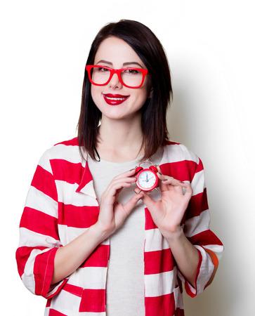 puntualidad: Portrait of a young woman in glasses with retro alarm clock Foto de archivo