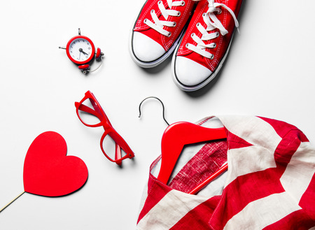 hangers: glasses, heart shaped toy, clock, gumshoes, jacket on the hanger and laptop on the white background