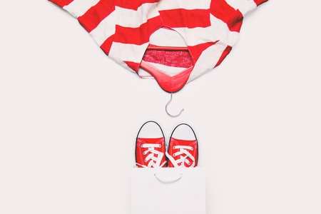 hangers: big red gumshoes in cool shopping bag and stried jacket on hanger Stock Photo