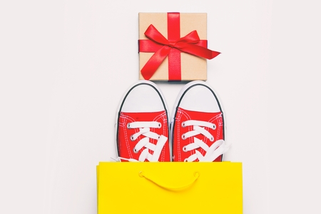 big red gumshoes in cool shopping bag and beautiful gift on the wonderful white background Stock Photo