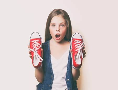 Young surprised girl with red gumshoes on white background Stock Photo