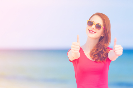 Redhead girl in the sunglasses on the beach