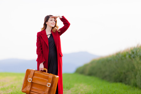 Portrait of young woman in red coar at autumn countryside with suitcase.