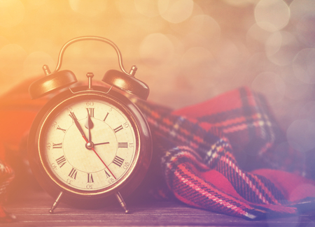 Alarm clock and scarf. Photo in retro color style.