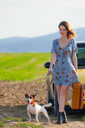 Portrait of young woman in dress with suitcase and dog near a yellow car at autumn countryside