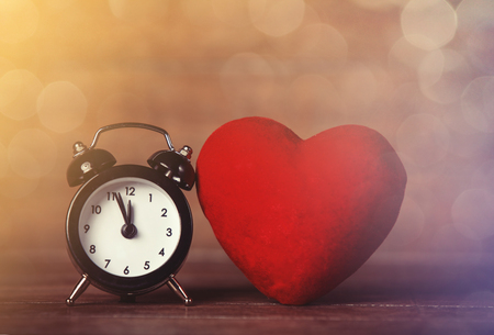 Retro alarm clock and heart shape on wooden table.
