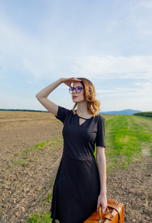 Portrait of young woman in black dress at autumn countryside with suitcase.