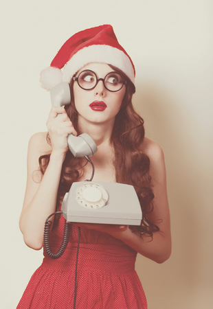 Beautiful brunette girl in christmas hat with telephone on yellow background. photo