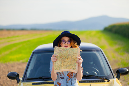 Portrait of young woman in dress with map near a yellow car at autumn countryside photo