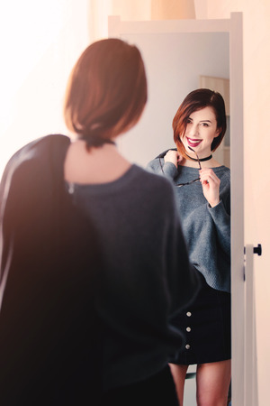 mirror image: beautiful young woman standing in front of mirror, holding a jacket and glasses and looking at her reflection
