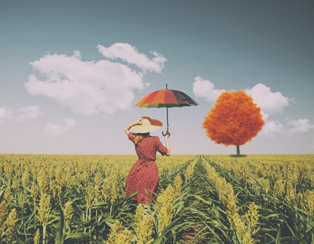 Girl with umbrella at corn field with autum tree at background