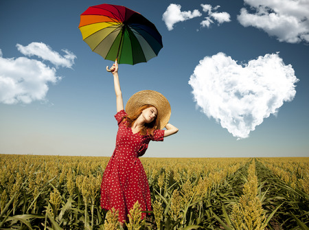Girl with umbrella at corn field with heart shape clouds Фото со стока