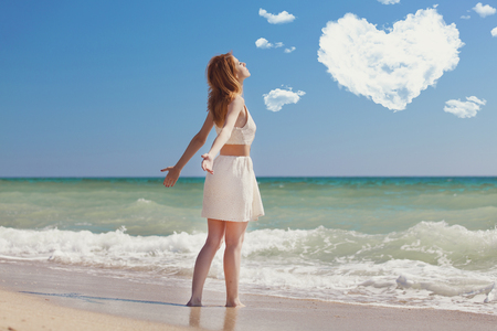 Young redhead girl at the beach with heart shape clouds Stock Photo