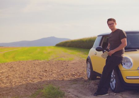 Young man with map standing near a car at countryside photo