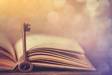 레트로 키 및 나무 테이블에 열린 된 책입니다.