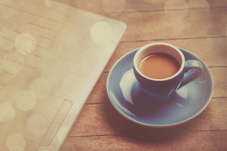 scratched: Cup of coffee and laptop on wooden table.