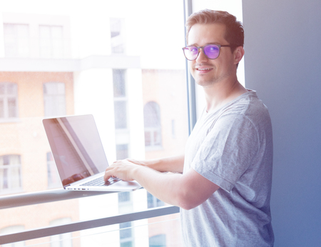 Handsome young freelancer man using laptop computer near a window. Freelance work, Business people concept photo