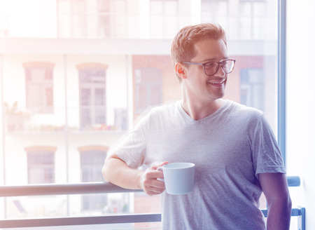 Handsome young freelancer man with cup of coffee standing near a window. photo