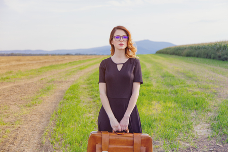 Portrait of young woman in black dress at autumn countryside with suitcase. photo