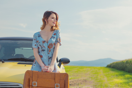 Portrait of young woman in dress with map and suitcase near a yellow car at autumn countryside Stock Photo