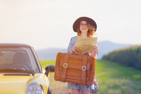 Portrait of young woman in dress with map and suitcase near a yellow car at autumn countryside photo